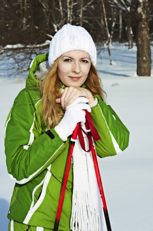 Woman tourist skier in snowy forest with ski poles photo