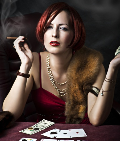 Fashion portrait of young adult woman with red hair in retro style - 30s,50s, 40s years. Player poker or fortune teller photo