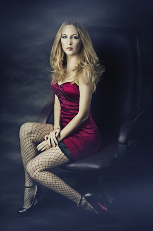 Beautiful blonde woman in sexy red dress and mesh stockings on long fit legs photo