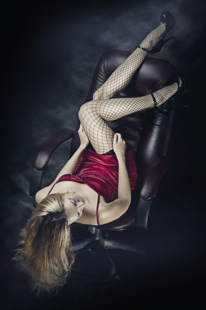 piernas sexys: Hermosa mujer rubia sexy vestido rojo y medias de malla mintiendo y está levantando las piernas hacia arriba