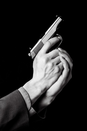 company secrets: Male hands with gun on black background Stock Photo