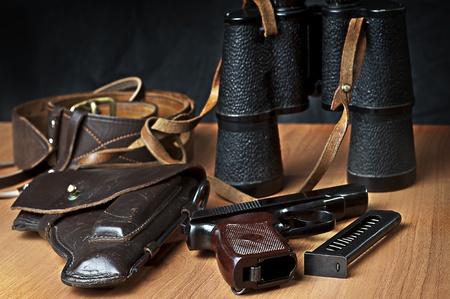 holster: Handgun on the table with holster, belt, binocular and empty pistol holder