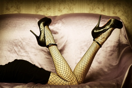 Sexy female legs in high heel black shoes and fishnet stockings. Retro style Stock Photo - 12633202