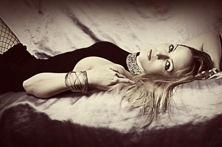Glamour blond woman with jewelry bracelet lying on silk sofa Stock Photo - 12633205