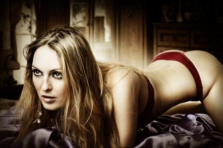 mujeres eroticas: Joven mujer sexy rubia en bikini en la cama, recostado en la cama Foto de archivo