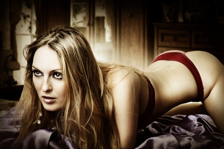 erotic girl: Young sexy blond woman in bikini at bedroom lying on bed