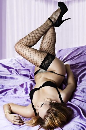 Sexy woman lying on silk violet bed in her bedroom. Black lingerie - bra, panties, lace stockings, fishnet and shoes with high heels Stock Photo