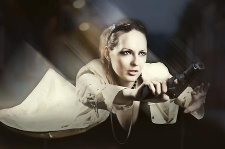handgun: Moving beautiful woman holding gun on night street