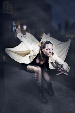 Portrait of beautiful woman with gun in white raincoat jumping on night european street photo