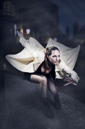 mujer con pistola: Retrato de mujer hermosa con una pistola en el salto impermeable blanco en la noche del European Street Foto de archivo