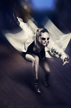 Portrait of beautiful woman with gun in white raincoat and designer sun glasses jumping on night  street. Motion Stock Photo - 12633231