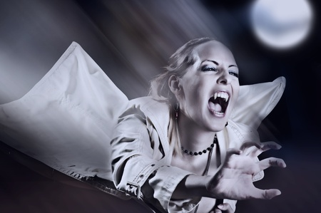 Angry female vampire with bangs attacking on night street photo