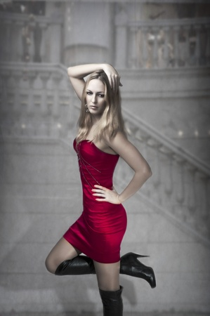 Fashion portrait of sexy  woman in high heel long black boots and fashionable red silk dress for party photo