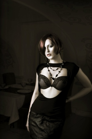 decolette: Young sexy woman with red hair on dark background Editorial