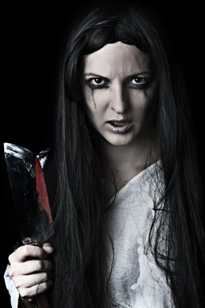 Portrait of a gory and scary zombie woman on black background with bloody knife photo