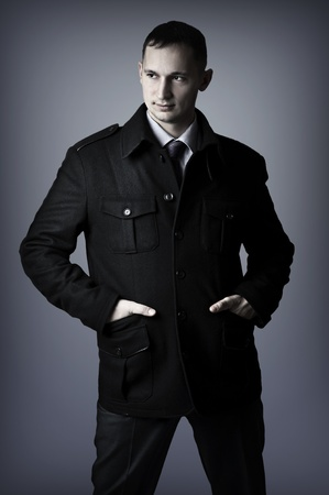 Young handsome sexy elegant business man in black coat photo