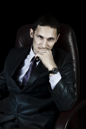 Handsome elegant businessman with chronographs on hand sitting on leather chair on black background