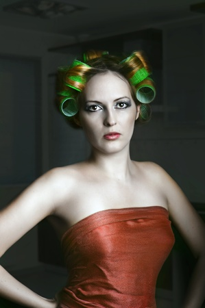 Young Attractive woman -  Housewife with green hair rolls  Stock Photo