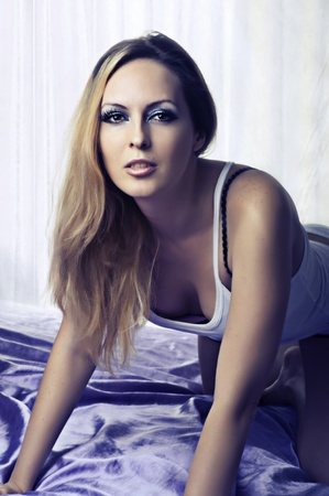 Sexy blond  woman on bed in bedroom in white t-shirt photo