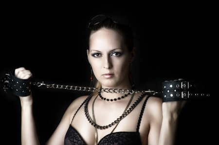 Sexy woman - lady or madam in bdsm play with handcuffs on black background Stock Photo - 12899439