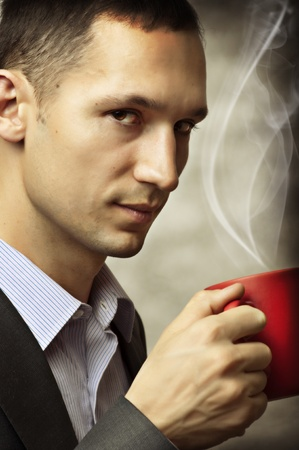 Closeup portrait of a young handsome man having a cup of coffee Stock Photo - 12899495