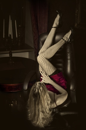 Sexy woman with long slim sexy legs is upside down on chair photo