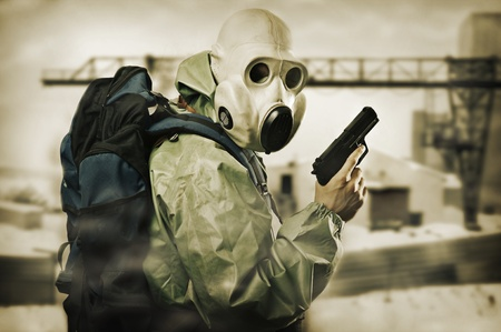 Post apocalypses world halloween concept. Portrait of man in gas mask with handgun  photo