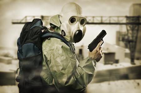 Post apocalypses world halloween concept. Portrait of man in gas mask with handgun  photo