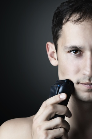 Fashion portrait of Young handsome man. male chin and electric shaver