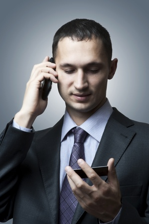 Handsome young business man with a mobile phone and a card Stock Photo - 12977912