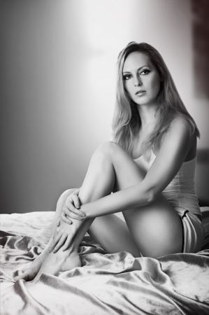 Beautiful woman sitting on bed in bedroom. Black and white photo
