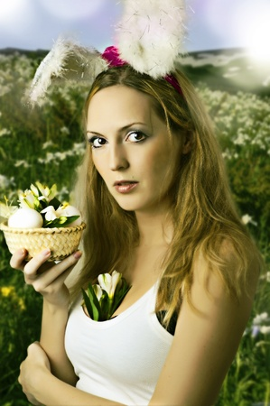 Sexy woman easter bunny on spring field with flowers Stock Photo - 12977949