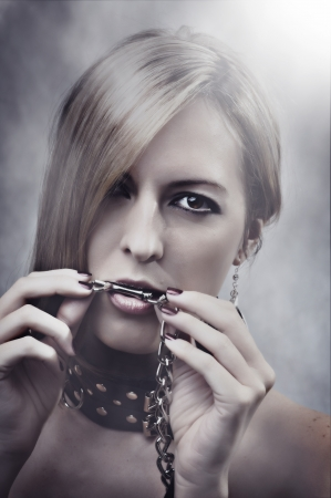 masochism: Beautiful Woman with chain in her mouth. Make up and manicure
