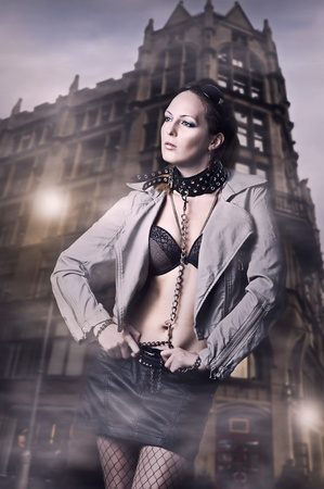 sadomasochism: Sexy woman in leather jacket and skirt in the city Stock Photo
