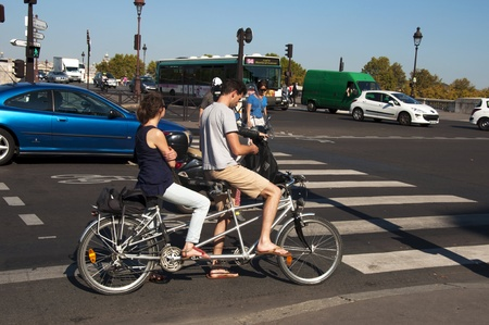PARIS - SEPTEMBER 29: Young couple on a tandem bike on September 29, 2011 in Paris.