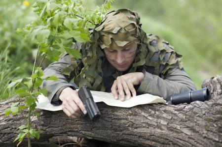 guerilla warfare: Military Camouflaged man in forest with black handgun, map and binocular Stock Photo