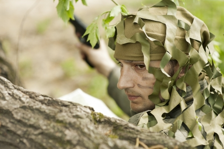 guerilla warfare: Young Camouflaged military man in forest with gun.