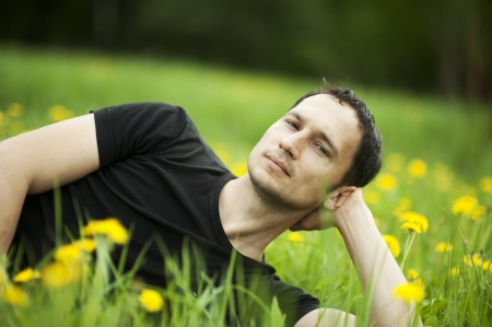 liying: Young beautiful guy student liying on a grass  Summer field with yellow flowers Stock Photo