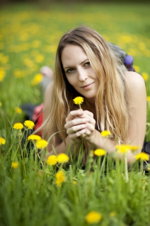 liying: Young beautiful girl student liying on a grass  Summer field with yellow flowers Stock Photo