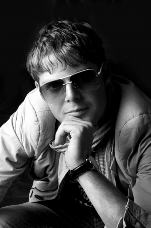 Black and white portrait of young fashion man in sun glasses photo