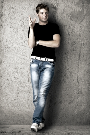 Young handsome man in black t-shirt and blue jeans is leaning against the wall