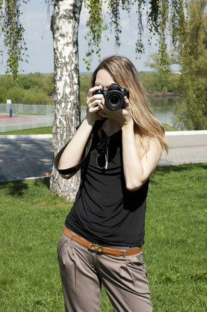 shootting:  Beautiful slim girl with camera on nature