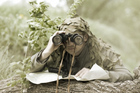 combative sport: Military Camouflaged man in forest with black handgu and binocular
