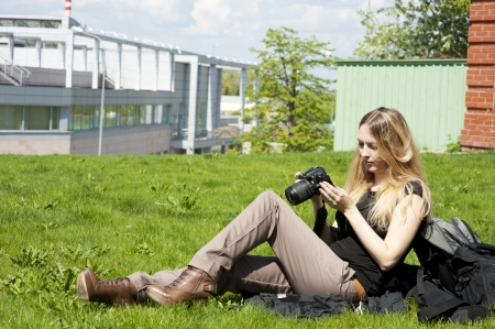 Young woman photographer  sitting on grass photo