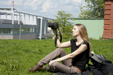 Young woman photographer  sitting on grass Stock Photo - 13815429