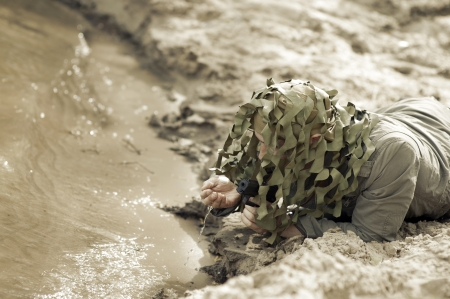 Military Camouflaged man with black handgu drink water from river photo
