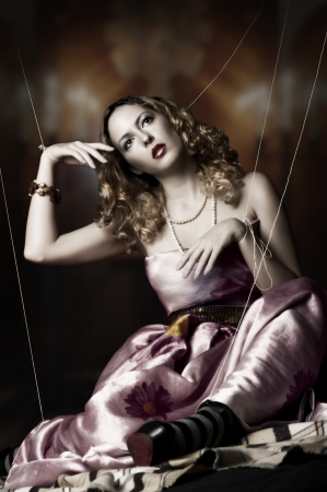 puppet woman: marionette on string. Fashion portrait of blond woman in puppet style