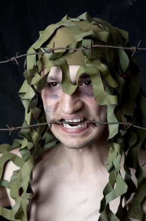 jailbreak: Military man - face closeup with barbed wire in his mouth
