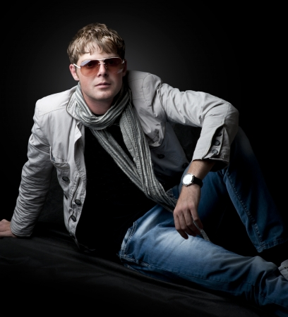 Young fashion man sitting on black background photo