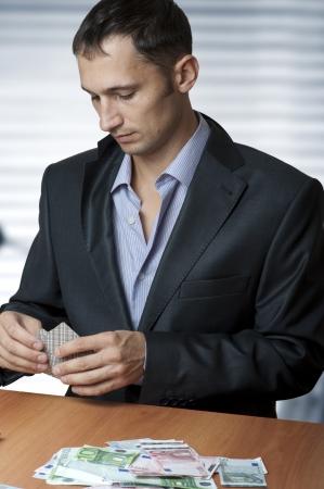 mucho dinero: Retrato de hombre adulto joven y apuesto a jugar al poker